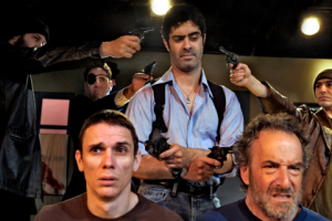 "Padraic (Damien Seperi, center) searches for answers in the death of his beloved cat in the Masquers Playhouse production of ""The Lieutenant pf Inishmore."" Padraic questions Joey (Alan Coyne, bottom left) and Donny (Avi Jacobson, bottom right) while under pressure from Brendan, Christy, and Joey (Jesse MacKinnon, David Stein, and Dan Kurtz). Photo Credit: Masquers Playhouse"