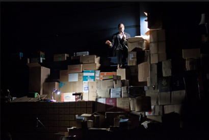 Geoff Sobelle with astonishing intimacy from the top of a mountain of boxes in
