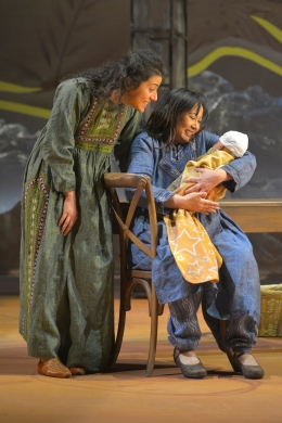 Mariam (Kate Rigg, seated) holds Laila's (Nadine Malouf) newborn child. Photo credit: Kevin Berne